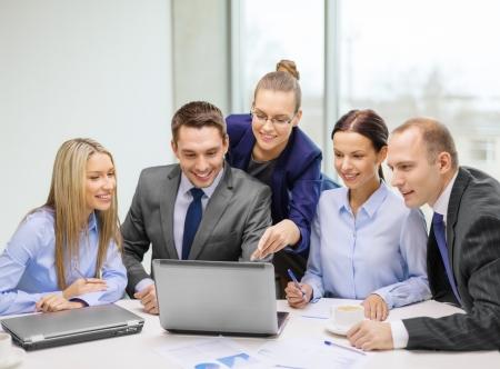 Negocios, la tecnología y el concepto de oficina - sonriendo equipo de negocios con ordenadores portátiles, documentos y café que tiene la discusión en la oficina Foto de archivo - 24489304
