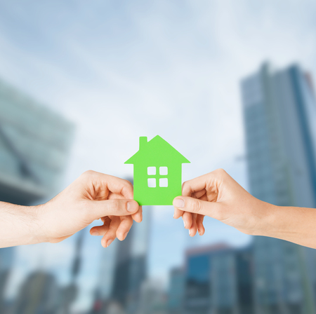 home protection: building, family and real estate concept - closeup picture of woman and man hands holding green house