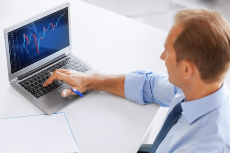 business, office and money concept - smiling businessman working with forex chart in office photo