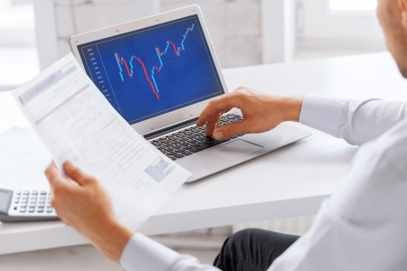 business, office and money concept - businessman working with forex chart and papers in office photo