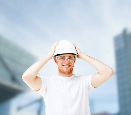 building, developing, consrtuction and architecture concept - picture of male architect in white helmet with safety glasses photo