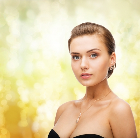 beauty and jewelry concept - woman wearing shiny diamond earrings and pendant Stock Photo - 24489830
