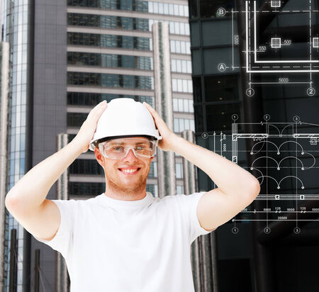 building, developing, consrtuction and architecture concept - male architect in white helmet with safety glasses photo