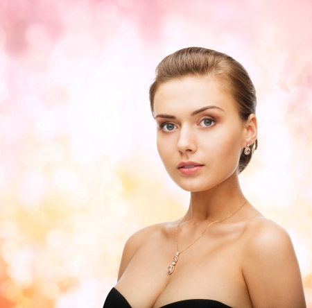 beauty and jewelry concept - woman wearing shiny diamond earrings and pendant Stock Photo - 24490376