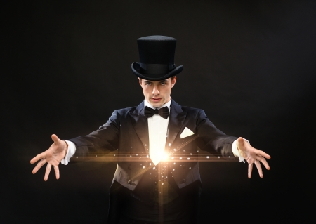 abracadabra: magic, performance, circus, show concept - magician in top hat showing trick