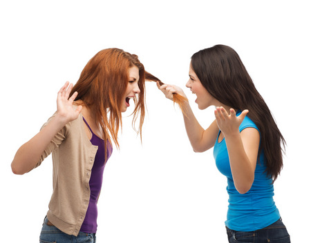 pulling hair: bullying, friendship and people concept - two teenagers having a fight and getting physical