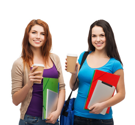 education, technology and people concept - two smiling students with bag, folders, tablet pc and takeaway coffee standing photo