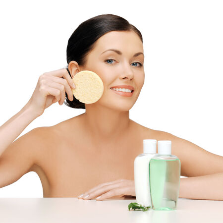 woman face cream: picture of woman with sponge and cosmetic bottles Stock Photo