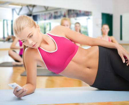 fat burning: woman lying on the floor and looking into smartphone in the gym Stock Photo