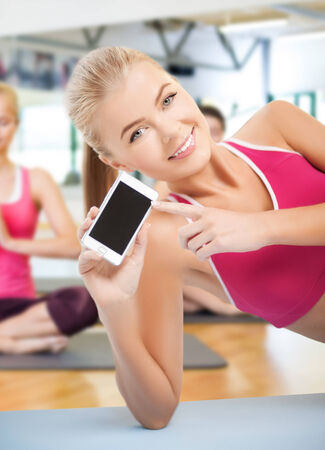 fat burning: woman lying on the floor and sowing smartphone Stock Photo