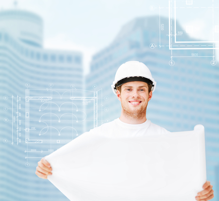male architect in white helmet with blueprint photo