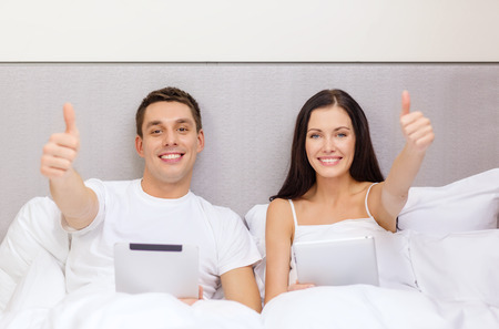 hotel, travel, relationships, technology, intermet and happiness concept - smiling couple in bed with tablet computers showing thumbs up photo