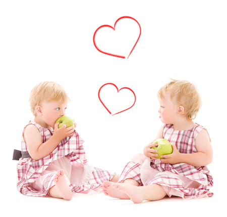 children and happiness concept - two adorable twins with apples over white photo