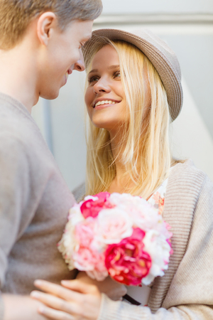 relationship love: summer holidays, love, relationship and dating concept - happy couple with bouquet of flowers in the city
