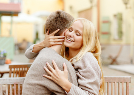 summer holidays, love, travel, tourism, relationship and dating concept - romantic happy couple hugging in the cafe photo