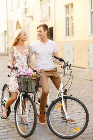 summer holidays, bikes, love, relationship and dating concept - smiling couple with bicycles in the city photo
