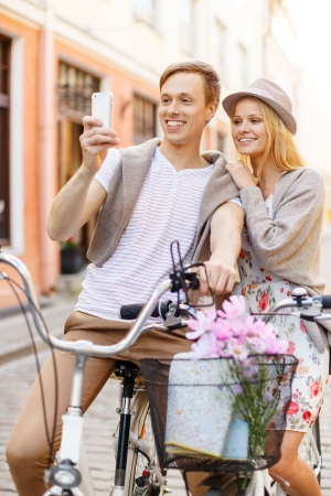 summer holidays, bikes, love, relationship, navigation, gps and dating concept - smiling couple with bicycles and smartphone in the city photo
