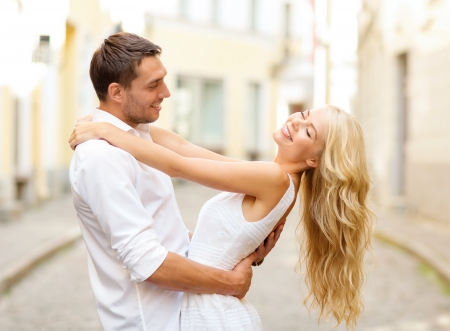 couple dancing: summer holidays, love, relationship and dating concept - smiling couple dancing in the city Stock Photo