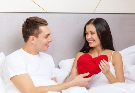 hotel, travel, relationships, holidays and happiness concept - smiling couple in bed with red heart-shaped pillow photo