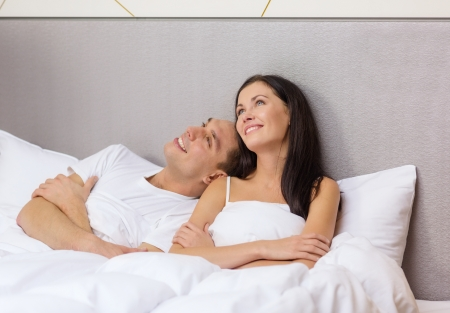 lying on bed: hotel, travel, relationships, and happiness concept - happy couple dreaming in bed Stock Photo