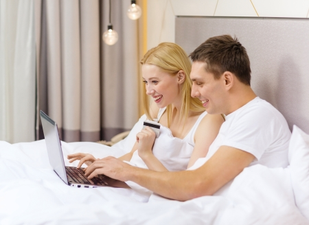 hotel, travel, relationships, technology, internet and happiness concept - smiling couple in bed with laptop and credit card photo