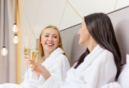 bachelorette party: hotel, travel, friendship and happiness concept - smiling girlfriends with champagne glasses in bed