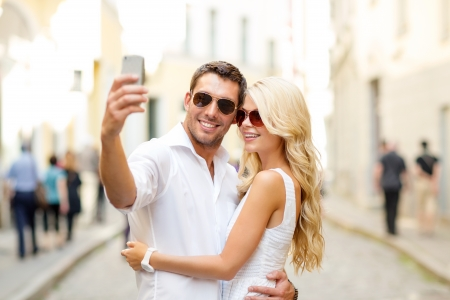 summer holidays, technology, love, relationship and dating concept - smiling couple taking picture with smartphone in the city photo