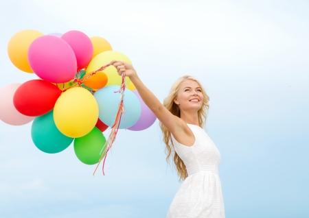 zomervakantie, concept viering en lifestyle - mooie vrouw met kleurrijke ballonnen buiten