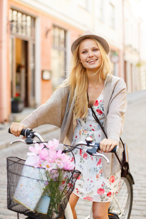 summer holidays, bikes, travel concept - attractive woman in hat with bicycle in the city photo