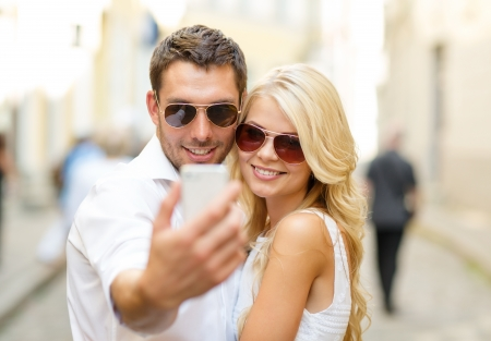 family picture: summer holidays, technology, love, relationship and dating concept - smiling couple taking picture with smartphone in the city