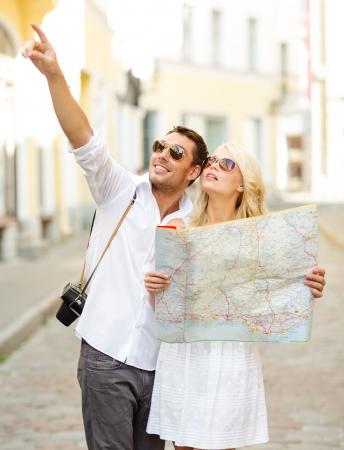 Touring: Wakacje letnie, randki i turystyka koncepcji - uśmiecha się para w okulary z map w mieście