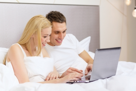 hotel, travel, relationships, technology, internet and happiness concept - smiling couple in bed with laptop photo