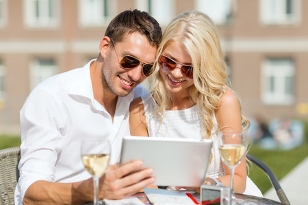 summer holidays, dating and technology concept - couple looking at tablet pc in cafe in the city photo