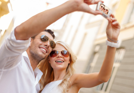 taking photograph: summer holidays, travel, vacation, tourism and dating concept - travelling couple taking photo picture with camera