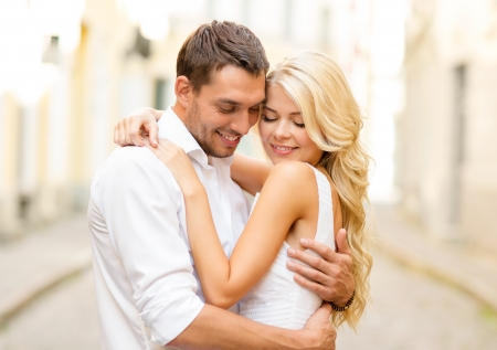 lovers embracing: summer holidays, love, travel, tourism, relationship and dating concept - romantic happy couple hugging in the street