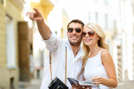 sightseeing tour: summer holidays, dating, city break and tourism concept - couple with camera and travellers guide