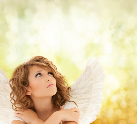holidays, love and costumes concept - unhappy teenage angel girl photo