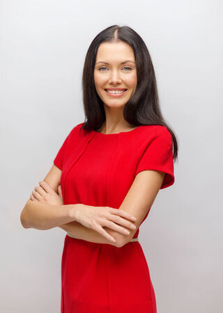 happiness and people concept - smiling young woman in red dress photo