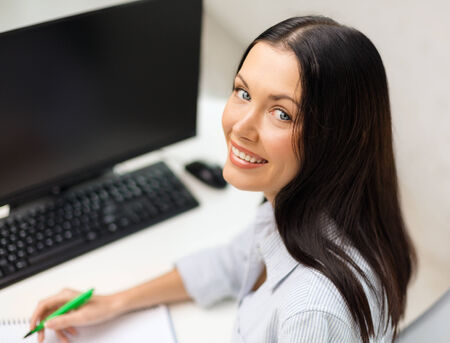 education, school, business and technology concept - smiling businesswoman or student studying photo