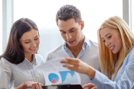 entrepreneurs: business and office concept - smiling business team looking at clipboard
