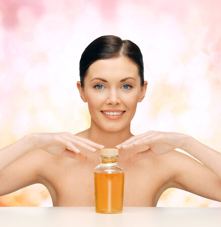 healthcare, spa and beauty concept - beautiful woman with oil bottle photo