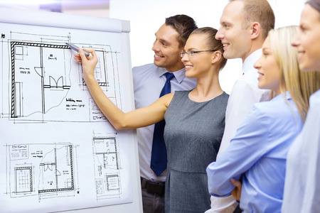 business, construction, building and office concept - smiling business team drawing blueprint on flip board and having discussion photo