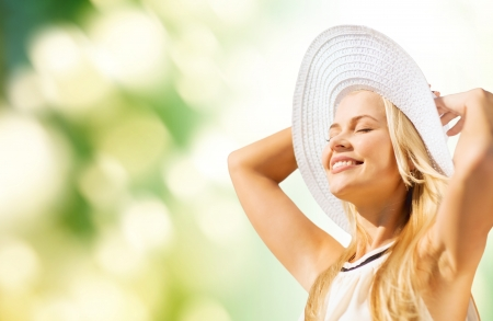 fashion and lifestyle concept - beautiful woman in hat enjoying summer outdoors photo