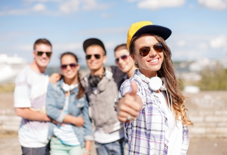 summer holidays and teenage concept - teenage girl in sunglasses, cap and headphones hanging out with friends outside and showing thumbs up photo