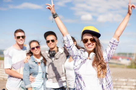 hing: summer holidays and teenage concept - teenage girl in sunglasses, cap and headphones hanging out with friends outside
