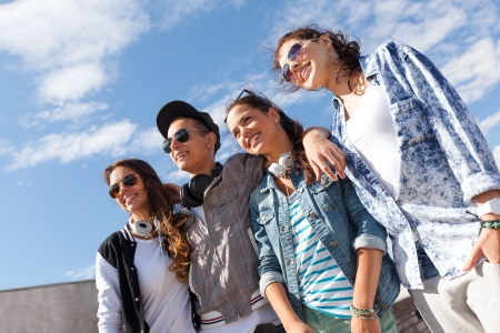 summer holidays and teenage concept - group of smiling teenagers in sunglasses hanging outside photo