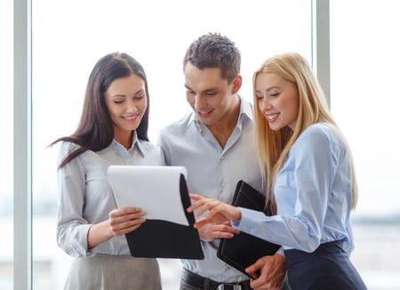 jonge ondernemers: bedrijfs-en kantoorconcept - lachend business team zoekt op klembord Stockfoto