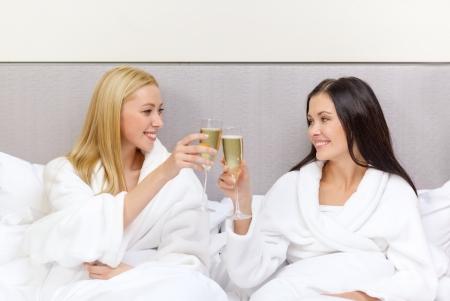 ホテル、旅行、友情、幸福のコンセプト - ベッドでシャンパン グラスのガール フレンドの笑みを浮かべて