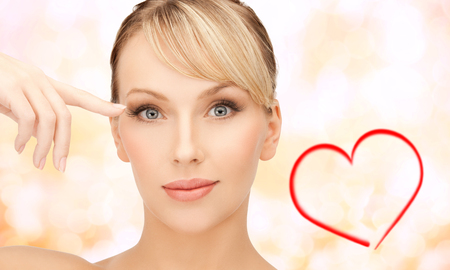health, spa and beauty concept - beautiful woman touching her eye area photo