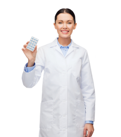 healthcare, medicine and pharmacy concept - smiling female doctor and with pills photo